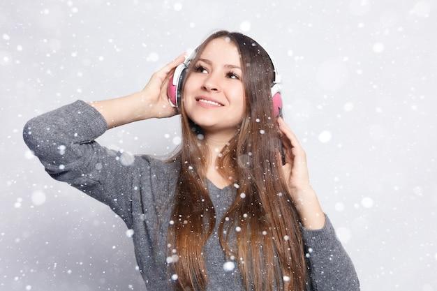 Neve, inverno, natale, persone, tempo libero e concetto di tecnologia - donna felice o ragazza adolescente in cuffia che ascolta la musica dallo smartphone e balla su sfondo di neve