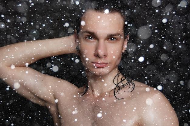 Neve, inverno, natale, persone, cura della pelle e concetto di bellezza - giovane bagnato con lunghi capelli neri su uno sfondo di neve nera. ritratto maschile con petto rasato. cura della pelle maschile.