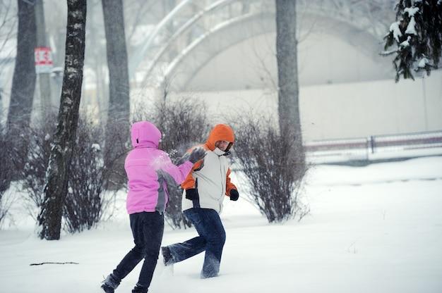 Battaglia a palle di neve. coppie di inverno che hanno divertimento giocando nella neve all'aperto