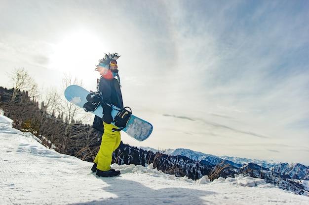 Snowboarder freerider in buffo cappello in montagna si sta preparando a scendere