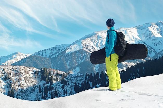 Snowboarder freerider in montagna si prepara a scendere sullo sfondo di montagne innevate