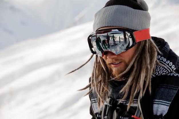 Ragazzo di snowboarder con i dreadlocks in piedi sul pendio con gli occhiali protettivi nella famosa località turistica di gudauri in georgia