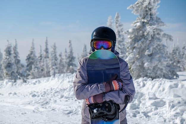 Snowboarder in un casco e occhiali tiene uno snowboard