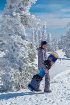 Snowboarder in casco sulla cima delle montagne