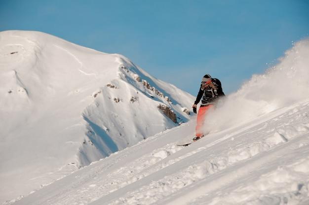 Uomo di snowboarder con i dreadlocks a cavallo giù per la collina nella famosa località turistica di gudauri in georgia