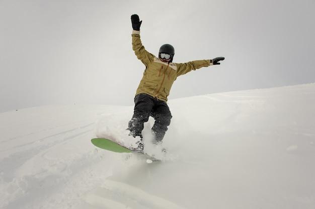 Snowboarder in sella giù per la collina tenendo le mani in alto nella famosa località turistica di gudauri in georgia