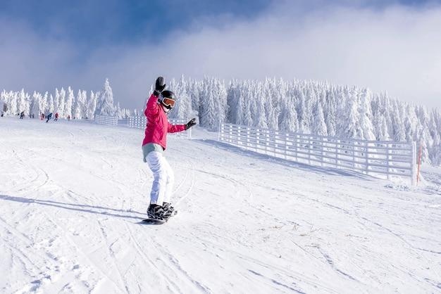 Snowboarder che guida giù per la collina nella località di montagna con alberi innevati sullo sfondo