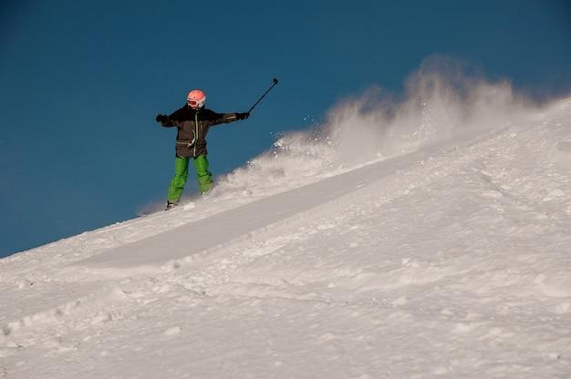 Snowboarder a cavallo giù per la collina con la fotocamera in mano nella famosa località turistica di gudauri in georgia