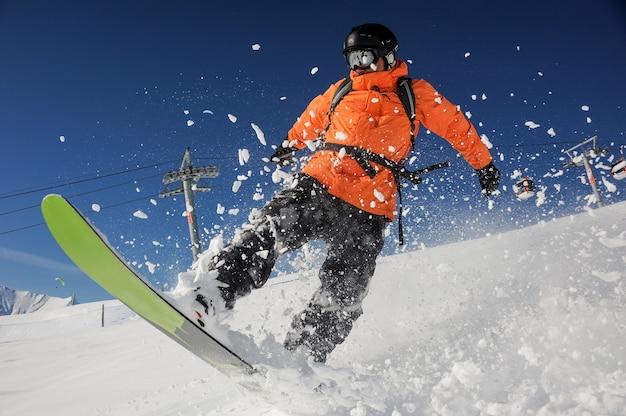 Snowboarder che guida giù la collina della montagna della polvere il giorno soleggiato. snowboard in georgia, goderdzi