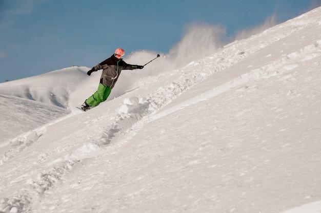 Snowboarder in sella lungo il pendio con la fotocamera in mano nella famosa località turistica di gudauri in georgia