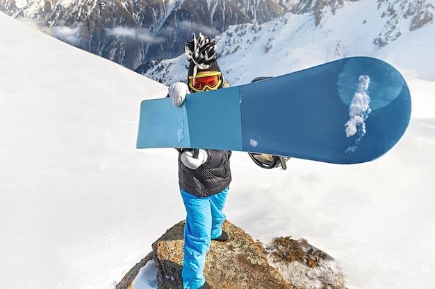Lo snowboarder in maschera da sci e cappello divertente tiene lo snowboard blu davanti alla telecamera. copia spazio