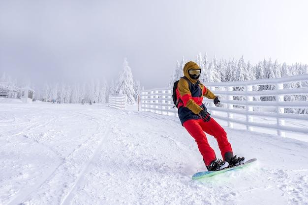 Snowboarder che scivola attraverso il pendio in una località di montagna