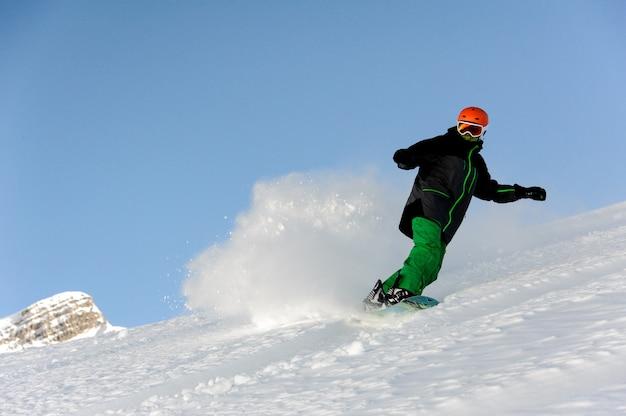 Snowboarder in tuta speciale scivola sulla montagna e solleva la neve dietro di lui
