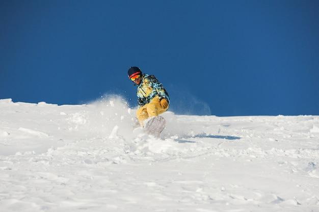 Snowboarder in abbigliamento sportivo alla moda che guida giù il pendio il giorno soleggiato in georgia, gudauri