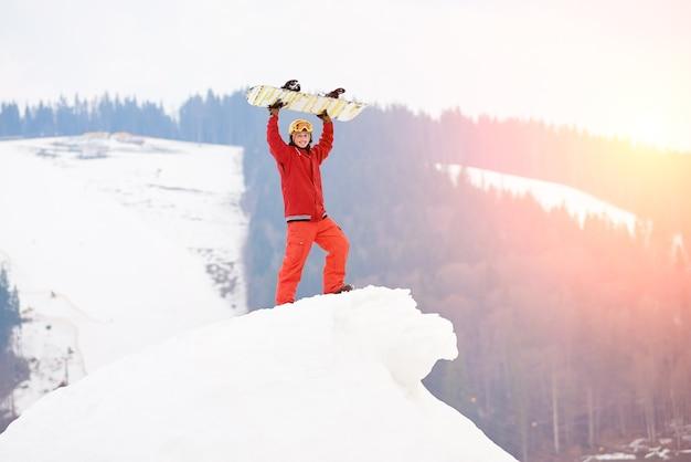 Snowboarder in cima al pendio innevato