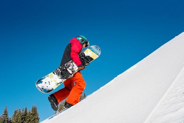 Snowboarder che cammina su per il pendio