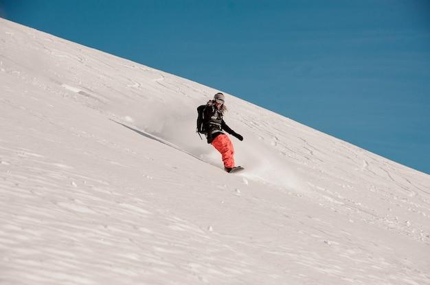 Snowboarder con i dreadlocks a cavallo giù per la collina nella famosa località turistica di gudauri in georgia