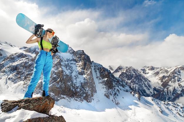 La donna dello snowboarder in bikini sul pendio guarda lontano contro le montagne innevate alla luce del sole