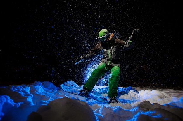 Donna dello snowboarder vestita con un abbigliamento sportivo verde che cavalca sul pendio della montagna nella notte sotto la luce blu