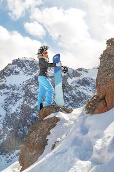 Donna dello snowboarder in cappello del mohawk in cima alla roccia in montagna nevosa. copia spazio