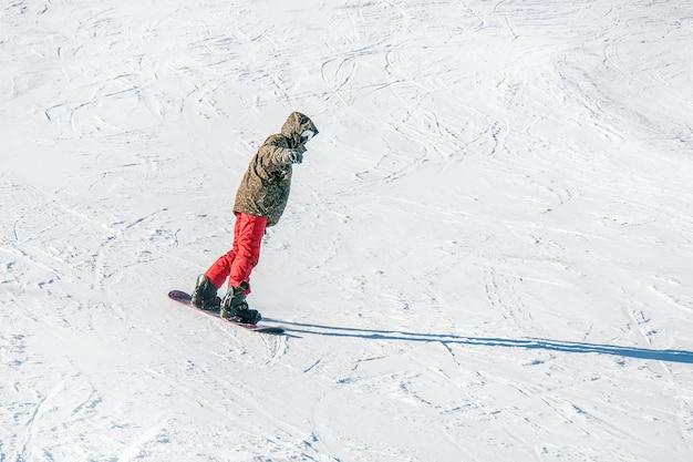 Snowboard in pantaloni rossi in montagna sullo sfondo della neve bianca..
