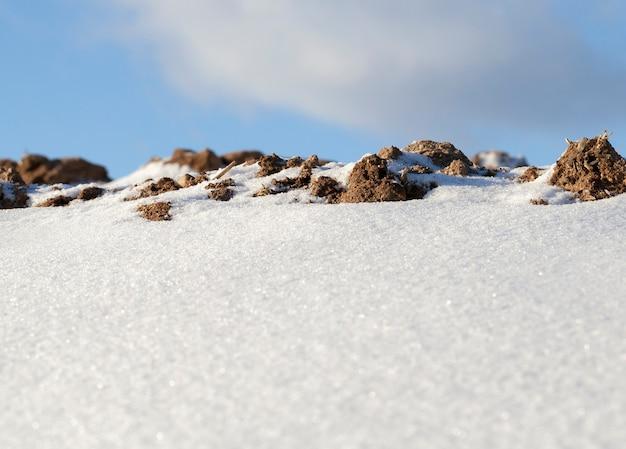 Cumuli di neve nella stagione invernale. cielo blu e primo piano di una foto. concentrati sul terreno vicino all'orizzonte