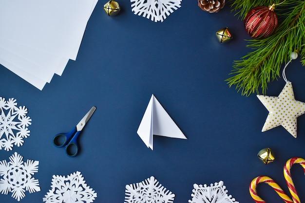 Il fiocco di neve è di carta. passaggio 5 piegare il foglio da sinistra. Foto Premium