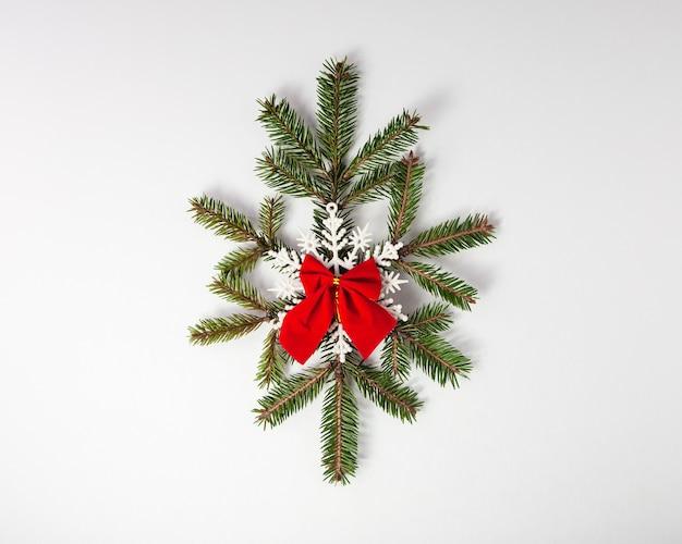 Fiocco di neve fatto di abete con fiocco di neve sulla parte superiore e nastro rosso decorazioni natalizie inverno legnoso piatto laici vista dall'alto