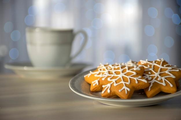Biscotti di pan di zenzero a forma di fiocco di neve sul piatto bianco nei raggi del sole del mattino con una tazza di tè sullo sfondo