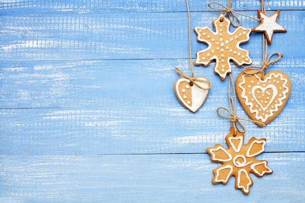 Fiocco di neve, stella e cuore del biscotto di panpepato di natale su sfondo blu. stile piatto. cucinare la cottura di capodanno