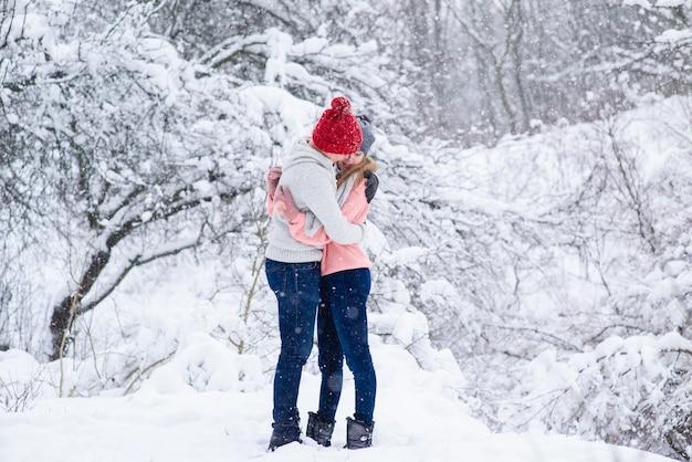 Fiocchi di neve intorno a donna e uomo innamorato