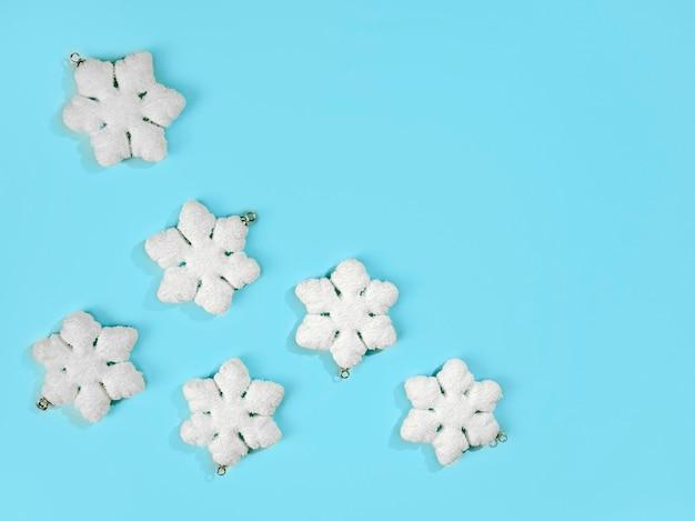 Fiocchi di neve su sfondo azzurro colori pastello composizione per le vacanze di natale spazio copia