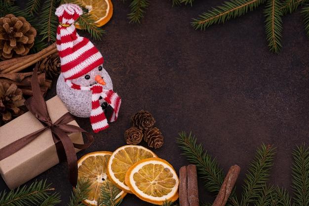 Pupazzo di neve e regalo sullo sfondo delle decorazioni natalizie
