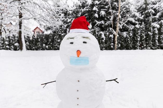 Pupazzo di neve in una maschera protettiva medica nella foresta