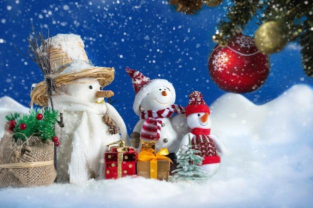 Pupazzo di neve in un cumulo di neve con regali e alberi di natale