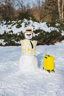 Pupazzo di neve con valigia pronto per il viaggio nello spazio della copia del paese tropicale