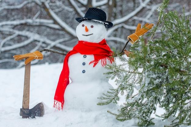 Boscaiolo pupazzo di neve con ascia nella foresta invernale