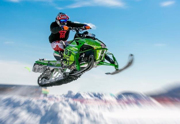 Cavaliere di motoslitta che salta attraverso la neve