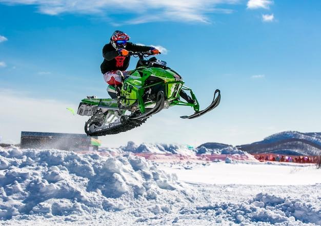 Cavaliere della motoslitta che salta attraverso la neve.