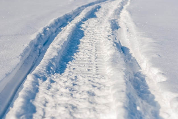 Sentiero in motoslitta su neve bianca profonda