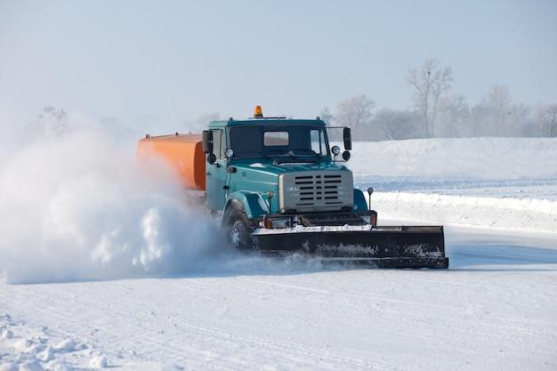 Lo spazzaneve sta pulendo una strada e la neve le vola intorno
