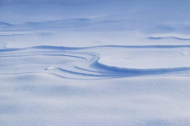 Sfondo innevato, superficie innevata della terra dopo una bufera di neve al mattino alla luce del sole con distinti strati di neve Foto Premium