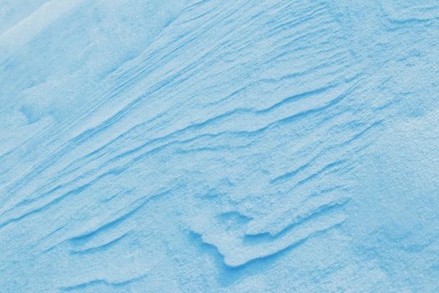 Sfondo innevato, superficie innevata della terra dopo una bufera di neve al mattino alla luce del sole con distinti strati di neve