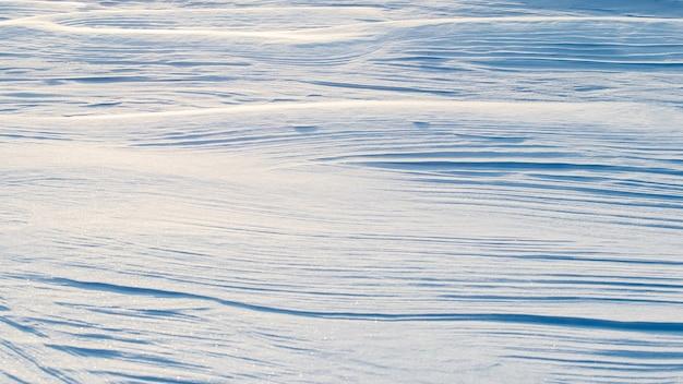 Sfondo innevato, superficie ondulata innevata della terra dopo una bufera di neve al mattino alla luce del sole