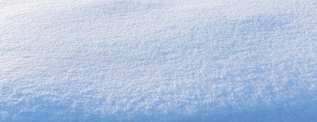 Sfondo innevato, superficie innevata con una trama di neve chiaramente espressa al sole mattutino