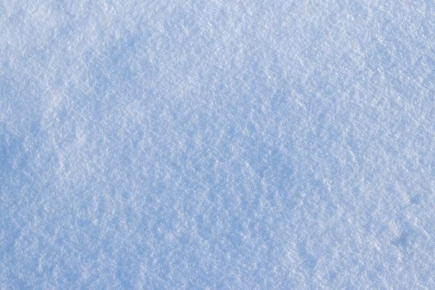 Sfondo innevato, superficie innevata con una trama di neve chiaramente espressa al sole mattutino Foto Premium