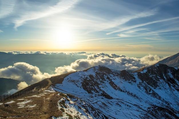 Alte montagne innevate attraverso le nuvole nel cielo azzurro al tramonto