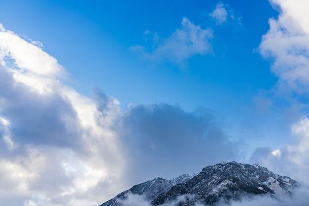 Picco di montagna innevato circondato da nuvole in una giornata di sole mattina con cielo blu.