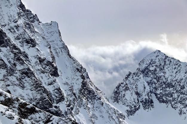 Picchi delle montagne innevate nel cielo blu delle nuvole caucaso