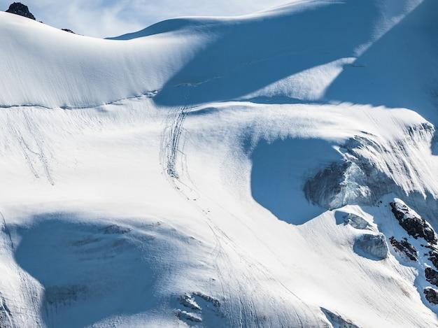 Montagna innevata all'aperto in inverno. paesaggio di cime innevate con tracce di pietre che cadono. montagne catturate nella neve, luogo ideale per gli sport estremi invernali.